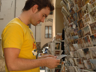 Guy looking at postcards